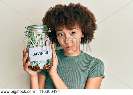 Young hispanic girl holding jar with savings skeptic and nervous, frowning upset because of problem. negative person.