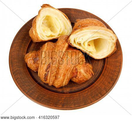 Croissant And Cut Croissant On A Clay Plate. Croissant Isolated On White Background.