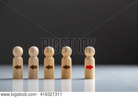 Wooden Dolls With Red Arrow Facing The Opposite Direction Black Arrows, Unique, Innovation And Creat