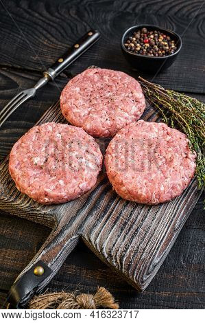Raw Chicken Turkey Patty, Ground Meat Cutlets On A Chopping Board. Black Wooden Background. Top View