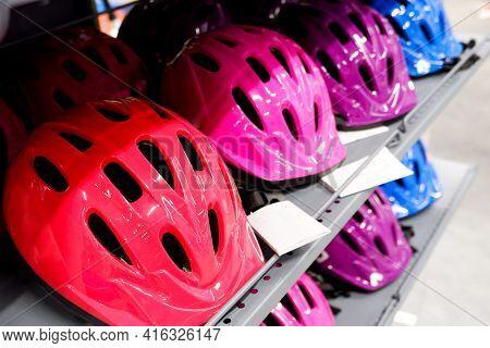 Various Colors Bike Helmets On Sport Store Display.