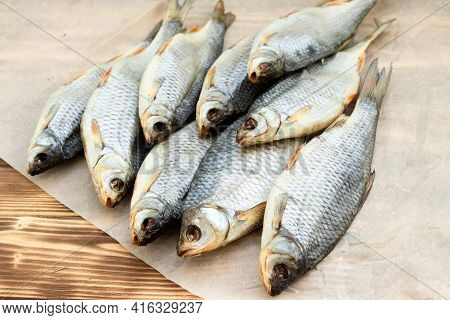 Fish Dry, Roach, Lies On A Wooden Table On Paper