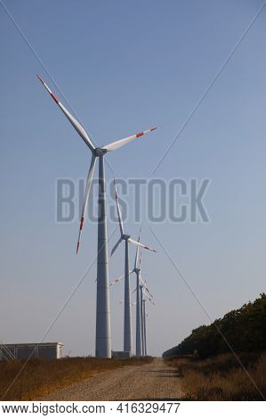 Row Of Windmills Spinning At Sunrise Against A Clear Blue Sky