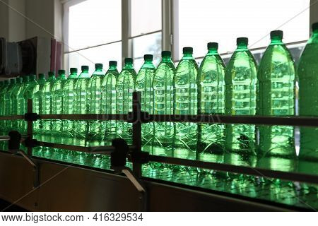 Conveyer Line With Plastic Bottles Filled With Mineral Water At The Plant For The Manufacture Of Bev