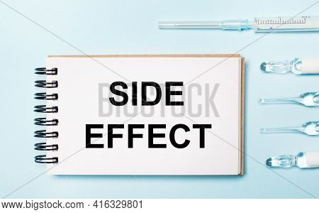 On A Blue Background Ampoule With Medicines And A Notebook With The Text Side Effect. Medical Concep