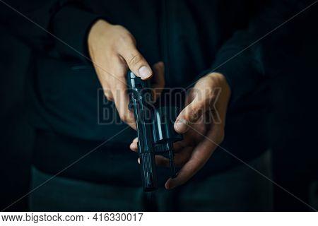 Close Up Of Man Reloading Revolver. Mens Hands Check For Bullets In Pistol Barrel. Person Prepares F