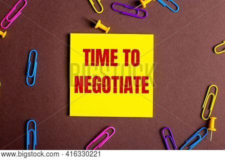 The Words Timr To Negotiate Is Written In Red On A Yellow Sticker On A Brown Background Next To Mult