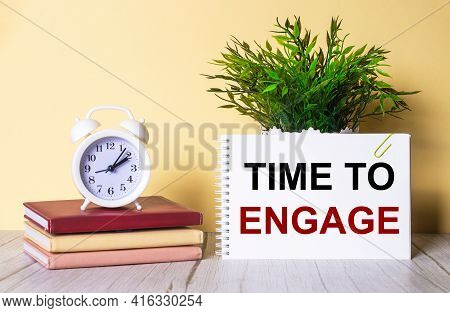 Time To Engage Is Written In A Notebook Next To A Green Plant And A White Alarm Clock, Which Stands