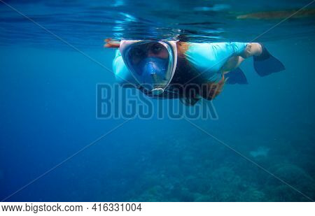 Woman In Full-face Mask Swimming In Blue Sea. Swimming In Blue Ocean Water. Young Woman Swimming On