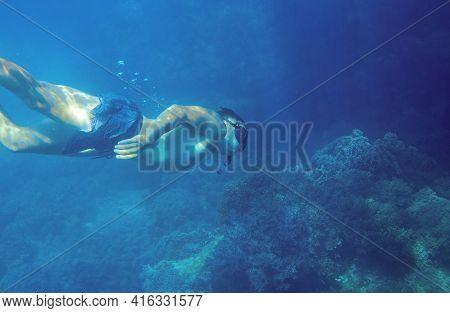 Man Diving In Deep Blue Sea. Young Snorkel Swims Underwater. Male Snorkel In Tropical Lagoon Underse