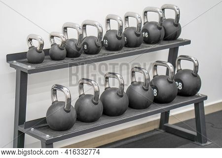 Several Black Weights Different Weights. Black Metal Weights Kettlebell One Row. Sports Kettlebells