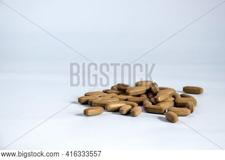 Natural Brown Pressed Medicinal Herb, Pills On Blue Background. Alternative Medicine Concept Of Drug