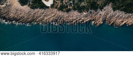 Aerial Top View Of Sea Waves Hitting Rocks On The Beach With Turquoise Sea Water. Amazing Rock Cliff