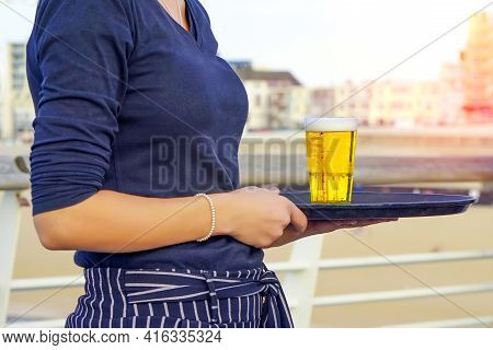 Waitress Carries A Glass Of Beer On A Tray At A Beach Restaurant. 2 September 2018. Den Haag. Nether