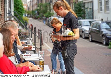 Waitress Takes The Customer's Order In The Restaurant. Lunch Time. Street Cafe In Amsterdam. 31 Augu