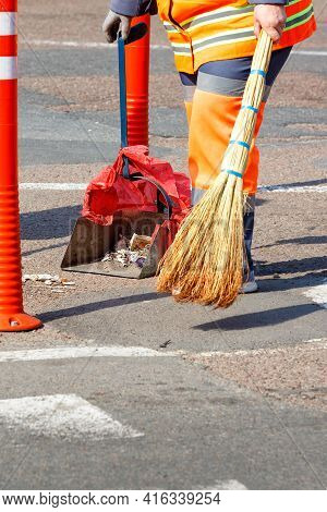 A Cleaning Lady In A Bright Orange Uniform Collects Trash From The Sidewalk On A Sunny Day. Vertical