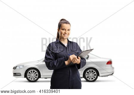 Female auto mechanic in front of a silver car holding a document and a clipboard isolated on white background