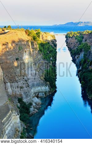 The Corinthian Narrow Canal In The Morning Haze Of A Summer Day Illuminates The Bright Rising Sun Of