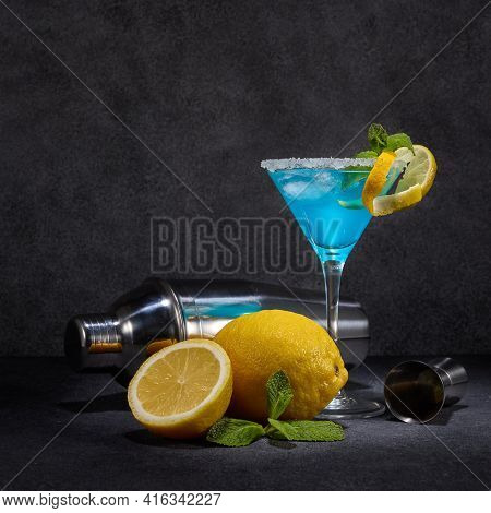 Glass with blue curacao cocktail, fresh mint and lemon, bar tools on dark grey background with copy space. Bar. Party. Blue cocktail.
