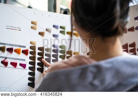 Focus At Color Chart. Young Pretty Asian Women Sitting Inside Hair Salon, Smiling While Choose New H