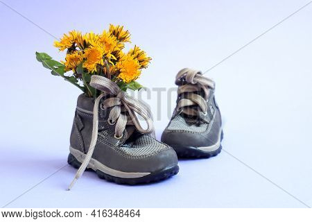 A Bouquet Of Yellow Dandelions In Gray Children's Shoes On A Blue Background, A Place For Text-the C