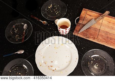 Top View Of Plates, Wooden Board And Dirty Cup With Leftover Cake, On A Black Table. Crumbs Scattere
