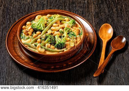 Vegetarian Coconut Curry With Chickpea, Green Beans, Cauliflower And Broccoli Florets In A Rustic Bo