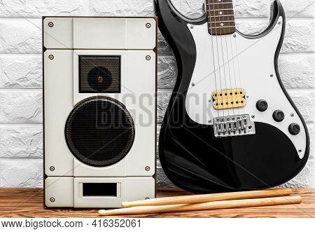 Guitar With Audio Speaker Near Brick Wall.
