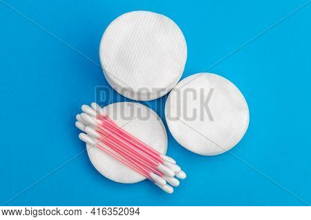 Cotton Pads With Ear Sticks On Blue Background.