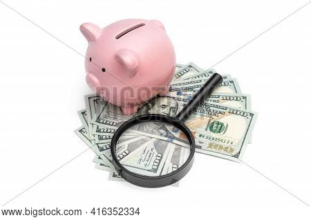 Piggy Bank With Money And Magnifying Glass On White.