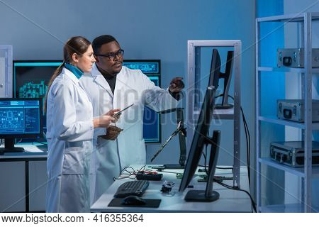 Diverse team of microelectronic engineers discuss current developments in a science lab. Workplace of microprocessor designers. The concept of innovations and inventions of the future.