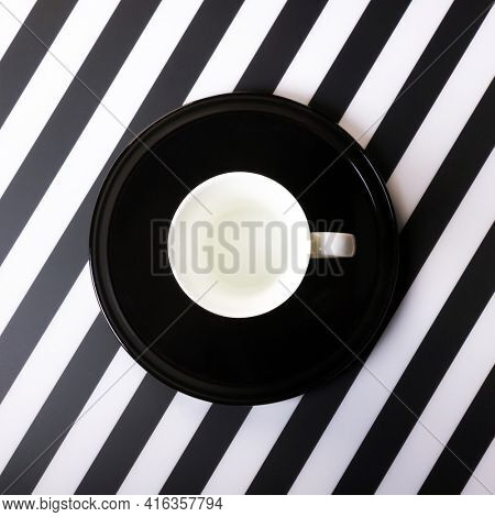 White cup on black plate on striped black and white mat. Top view.
