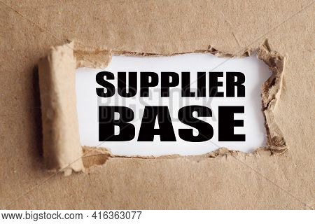 Supplier Base. Text On White Paper Over Torn Paper Background.