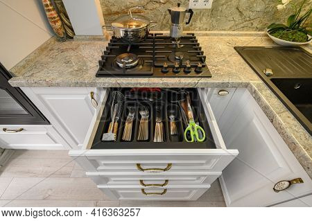 Row o drawers with kitchen utensils and silverware pulled out at modern classic white kitchen furniture, low angle shot