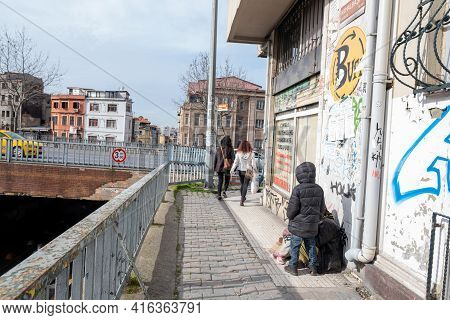 Taksim, Istanbul, Turkey - 03.12.2021: Turkish Beggars And A Child Standing And Looking People Peopl