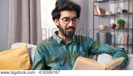 Close Up Portrait Of Hindu Young Cheerful Happy Handsome Guy In Glasses Sitting On Sofa At Home Alon