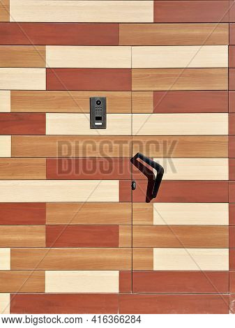 Background Of A Street Door Made Of Wooden Slats Of Different Colors, A Black Doorknob And A Modern