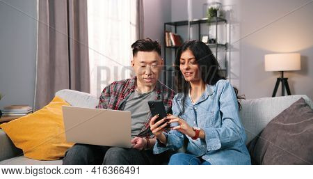 Multi-ethnic Married Couple Sitting On Couch In Cozy Living Room At Home Using Tech Digital Gadgets.