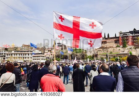 Tbilisi, Georgia - 9th April, 2021: Person Holds Georgian Flag In Street In Peaceful Protest.