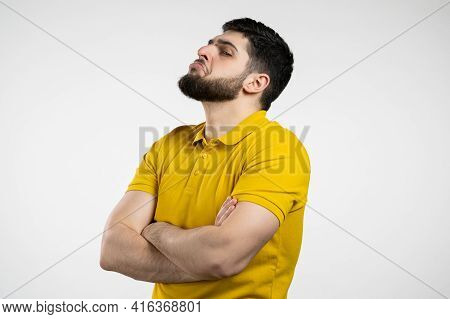 Angry Offended Man Keeping Arms Crossed And Staring At Camera With Sceptical And Distrustful Look, F