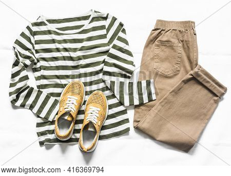 Women's Slouchy Pants, A Long Sleeve Striped Cotton T-shirt And Suede Sneakers On A Light Background