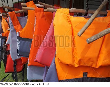Colorful Water Life Vest. Life Jackets Hanging On Clothes Line. Buoyancy Jackets On A Rail. Water Sp