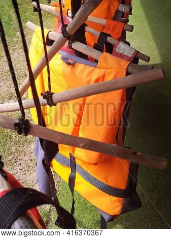 Life Jackets For Buoyancy Hung On Rustic Wooden Hangers. Water Sports Safety Accessory. Sports Equip