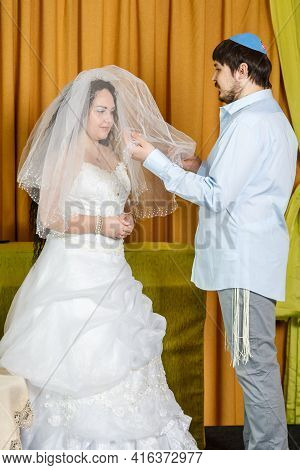 During The Chuppah Ceremony At A Synagogue Wedding, The Groom Covers The Bride With A Veil In The Ba