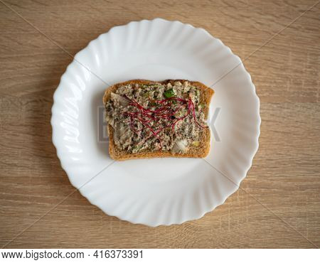Healthy, Tasty Sandwich With Dark Bread, Fish Paste, Avocado And Beetroot Alfalfa Sprouts On A White
