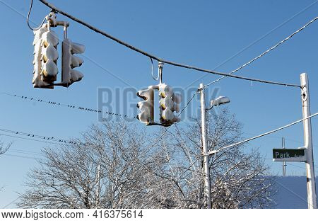 Two Traffic Lights Hanging From A Wire Are Filled With Snow After A Blizzard.
