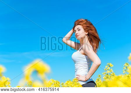 Freedom Concept. Young Happy Woman In Green Field. Blue Sky Behind. Beauty Girl Outdoors Enjoying Na