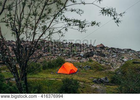 Beautiful View Through Tree Branches On Vivid Orange Tent Near Mountain Lake Water. Atmospheric Land
