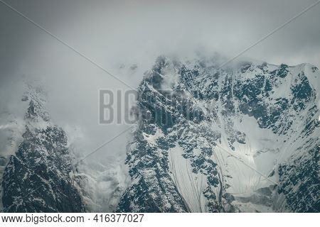 Awesome Mountain Landscape With Great Snowy Mountain Top In Cloudy Sky. Atmospheric Overcast Scenery