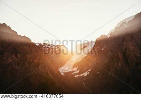 Golden Rays Of Rising Sun On High Snowy Mountain Top With Glacier. Beautiful Morning Landscape With